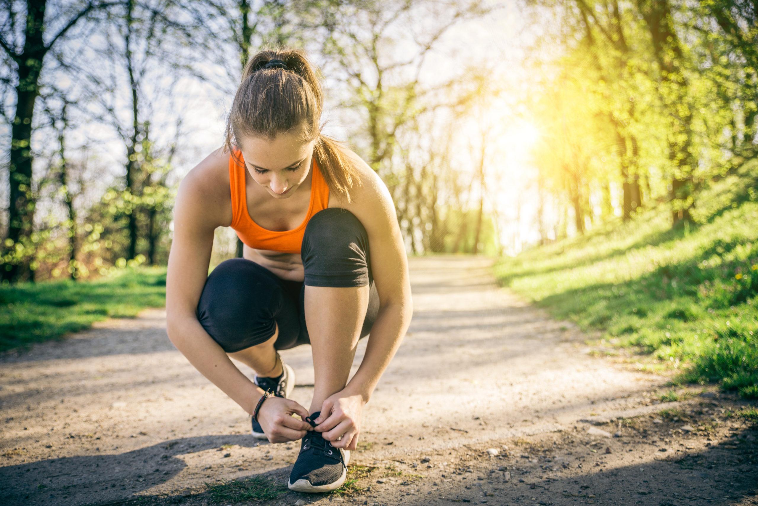 Female runner pausing to tie her shoe
